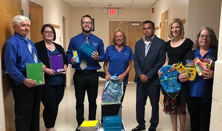 Jersey Shore Staff Holding School Supplies With School Staff