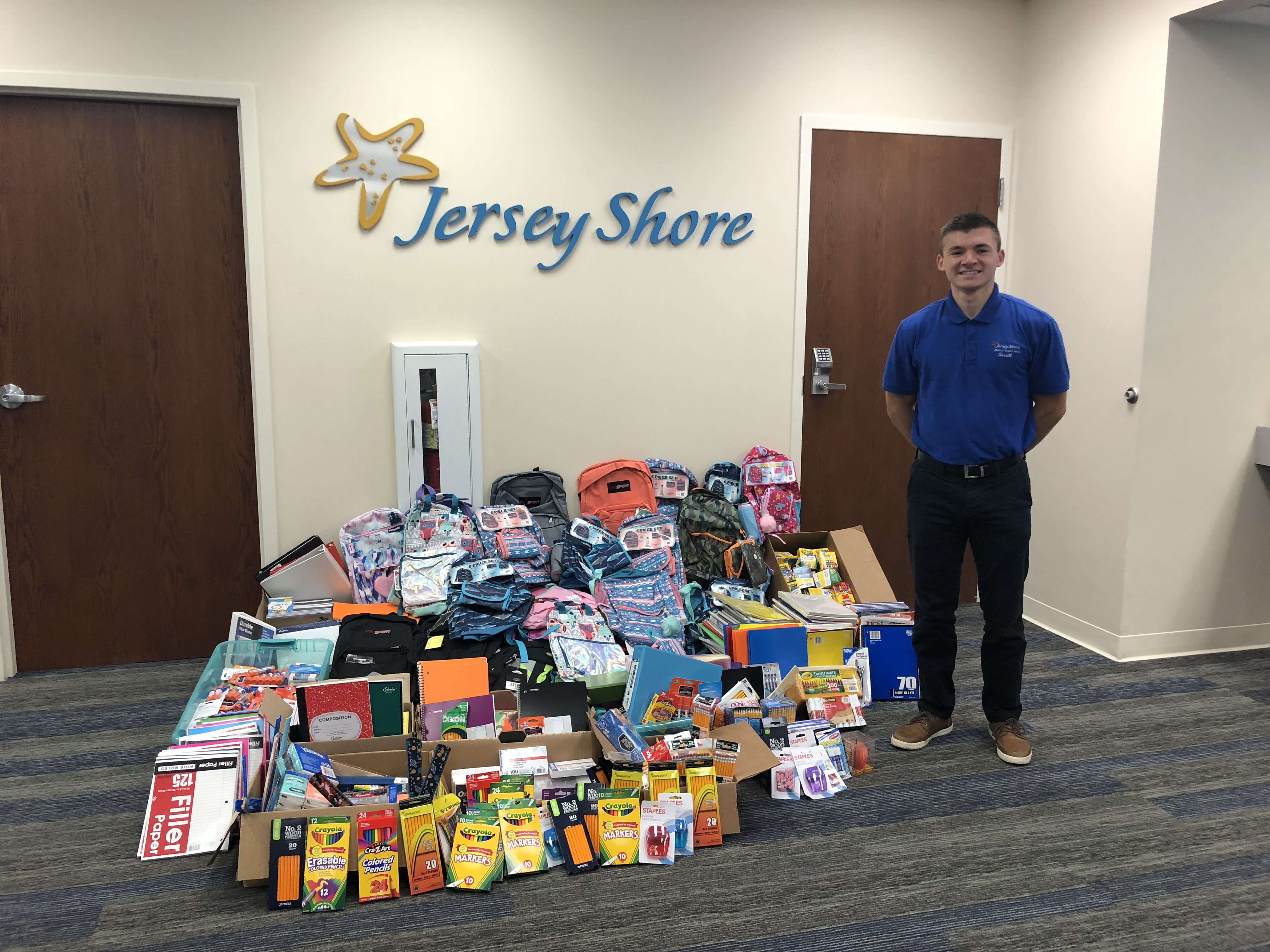 Staff member Garrett standing with donated school supplies