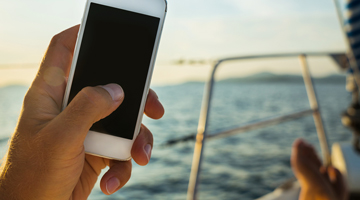 hand with mobile phone on boat