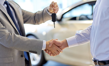 car dealer shaking hands and passing car keys to man