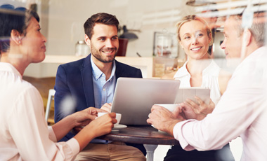 small business team sitting at table with laptop