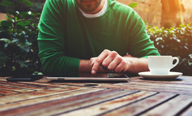 man using tablet outside on table with coffee