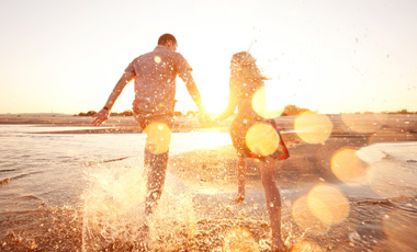 couple splashing in water on beach at sunset