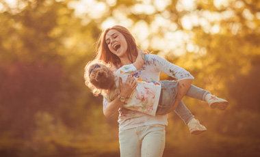 mom holding young girl laughing in park