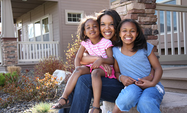 mom with two kids smiling on porch