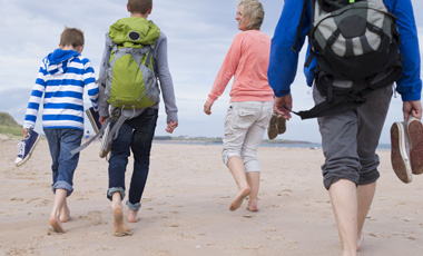 family walking on beach in cool weather