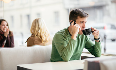 man on mobile phone in cafe while drinking coffee