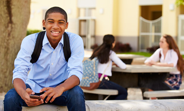 student smiling on bench with bookbag