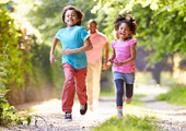 two children running with father in background