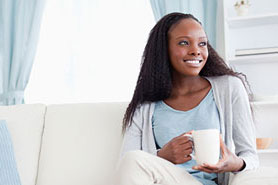 young african american woman drinking coffee on couch