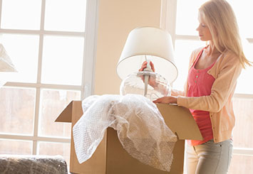 woman unpacking lamp in new home
