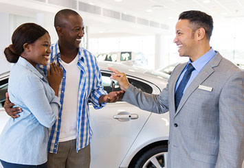 couple with car salesman in dealership